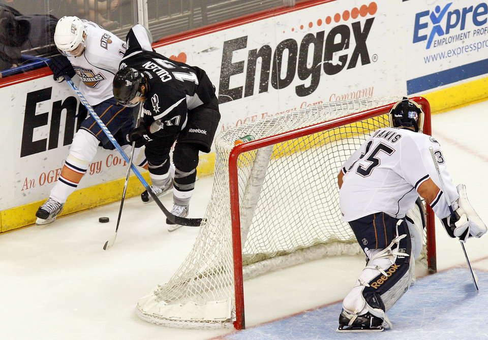 Oklahoma City's Magnus Paajarvi (16) and San Antonio's Mark Cullen (17) battle for the puck as Oklahoma City goalie Yann Danis (35) looks on during Game 1in the second round of the AHL hockey playoffs between the Oklahoma City Barons and the San Antonio Rampage at the Cox Convention Center in Oklahoma City, Thursday, May 3, 2012. Photo by Nate Billings, The Oklahoman