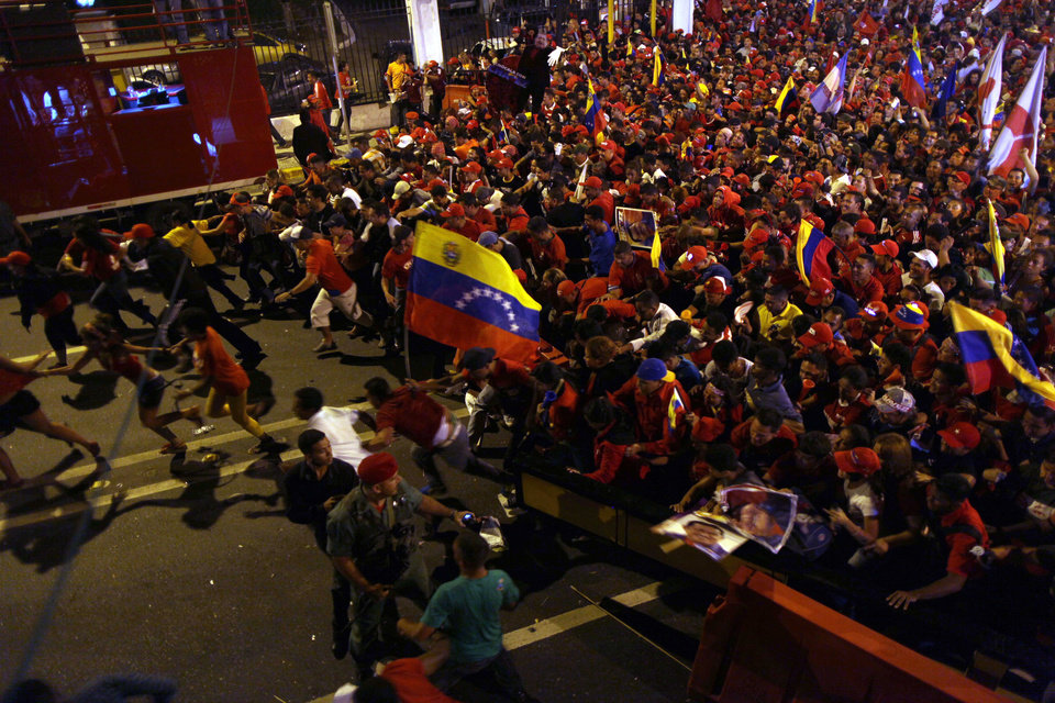 Supporters of President Hugo Chavez ran towards the Miraflores presidential palace as they celebrate in Caracas, Venezuela, Sunday, Oct. 7, 2012. Venezuela's electoral council said late Sunday President Hugo Chavez has won re-election, defeating challenger Henrique Capriles. (AP Photo/Rodrigo Abd)