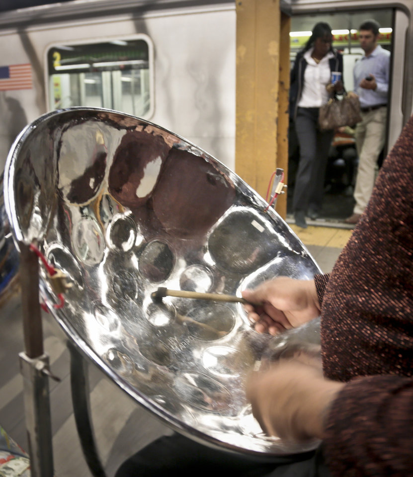 Photo - In this Wednesday, Oct. 9, 2013, photo, Roland Richards, foreground, plays a steel drum on the 34th Street subway platform in New York. Richards, who immigrated from Trinidad and brought the indigenous pan music as well, says he is a professional welder by trade.