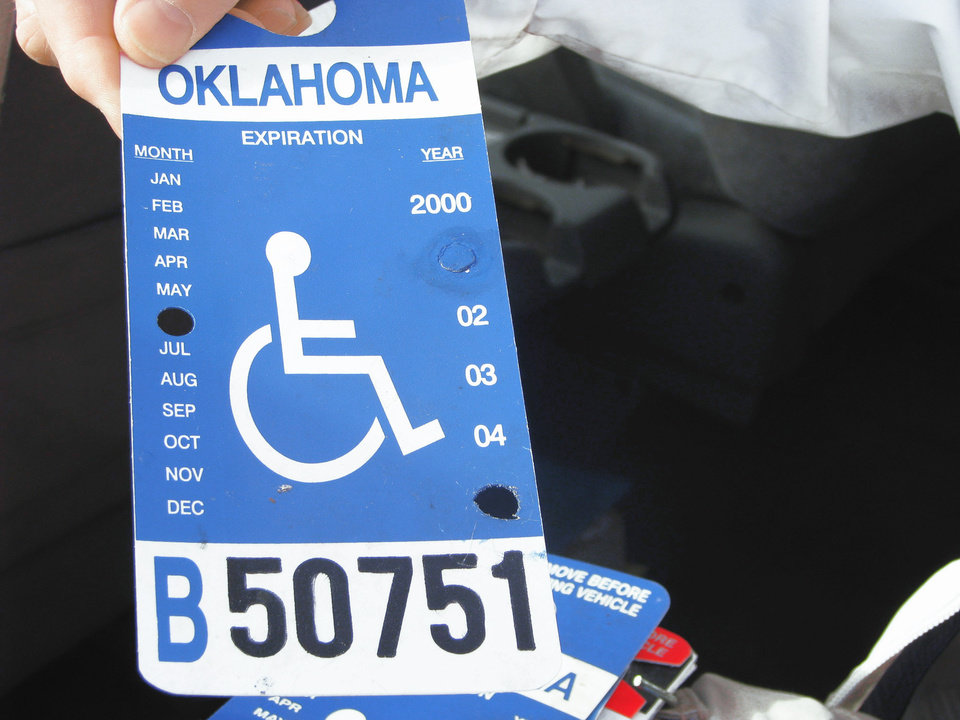 Photo - David Hoff, civilian officer for the Handicap Parking Enforcement Specialist program, holds bogus handicap parking placards he confiscated.  PHOTO BY VALLERY BROWN, THE OKLAHOMAN Steven Stokes Director, Oklahoma Office of Disability Concerns