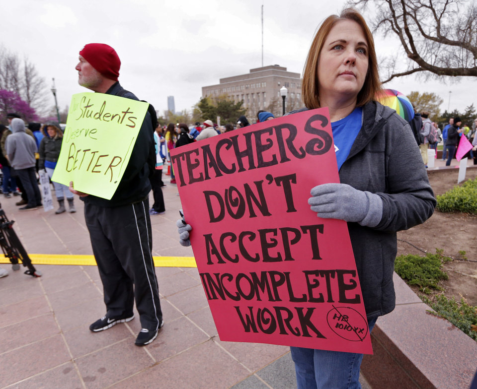 Photo - Sherry Dew, Southeast High School teacher carries a sign as Oklahoma teachers hold a rally at the State Capitol on Monday, April 2, 2018 in Oklahoma City, Okla.  Photo by Steve Sisney, The Oklahoman