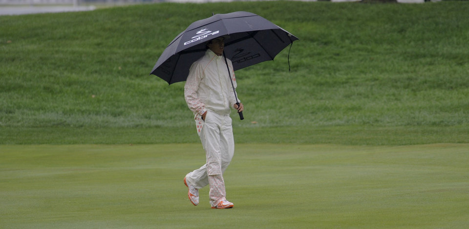 Photo - Rickie Fowler walks on the first green under an umbrella as rain falls during the final round of the BMW Championship golf tournament at Conway Farms Golf Club in Lake Forest, Ill., Sunday Sept. 15, 2013. (AP Photo/Matt Marton)