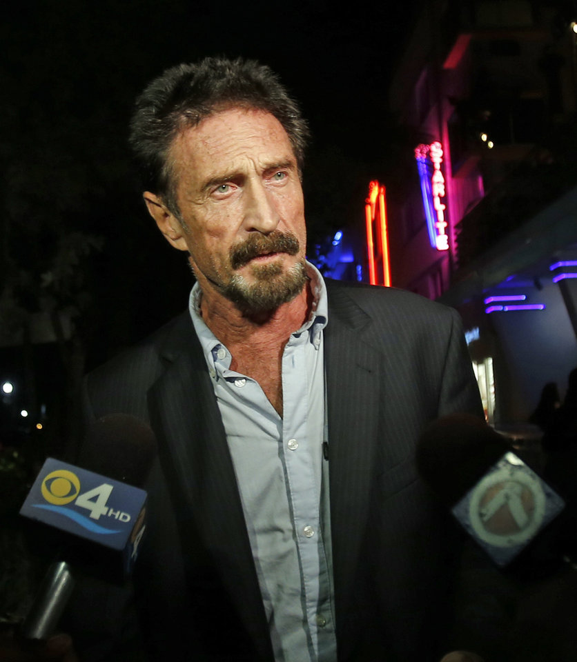 Anti-virus software founder John McAfee answers questions to reporters as he walks on Ocean Drive in the South Beach area of Miami Beach, Fla., Wednesday, Dec 12, 2012. McAfee arrived in the U.S. on Wednesday night after being deported from Guatemala, where he had sought refuge to evade police questioning in the killing of a man in neighboring Belize. (AP Photo/Alan Diaz)