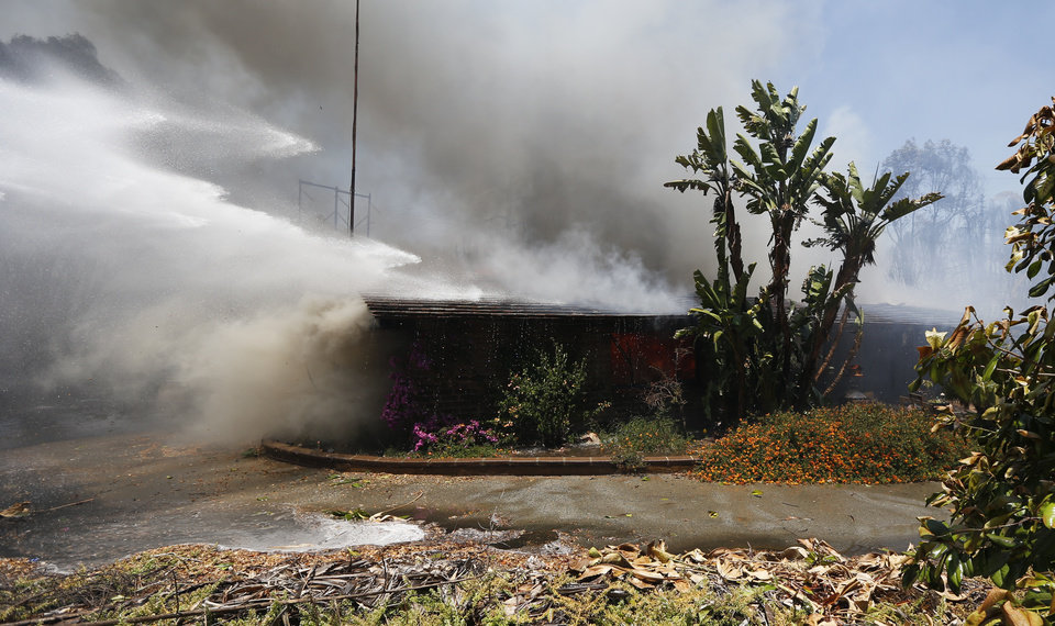 Photo - Powerful streams of water mix with billowing smoke from a home as a wildfire burns Wednesday, May 14, 2014, in Carlsbad, Calif.  Carlsbad city officials said mandatory evacuations were in progress Wednesday, and more than 11,000 notices were sent to homes and businesses. (AP Photo)