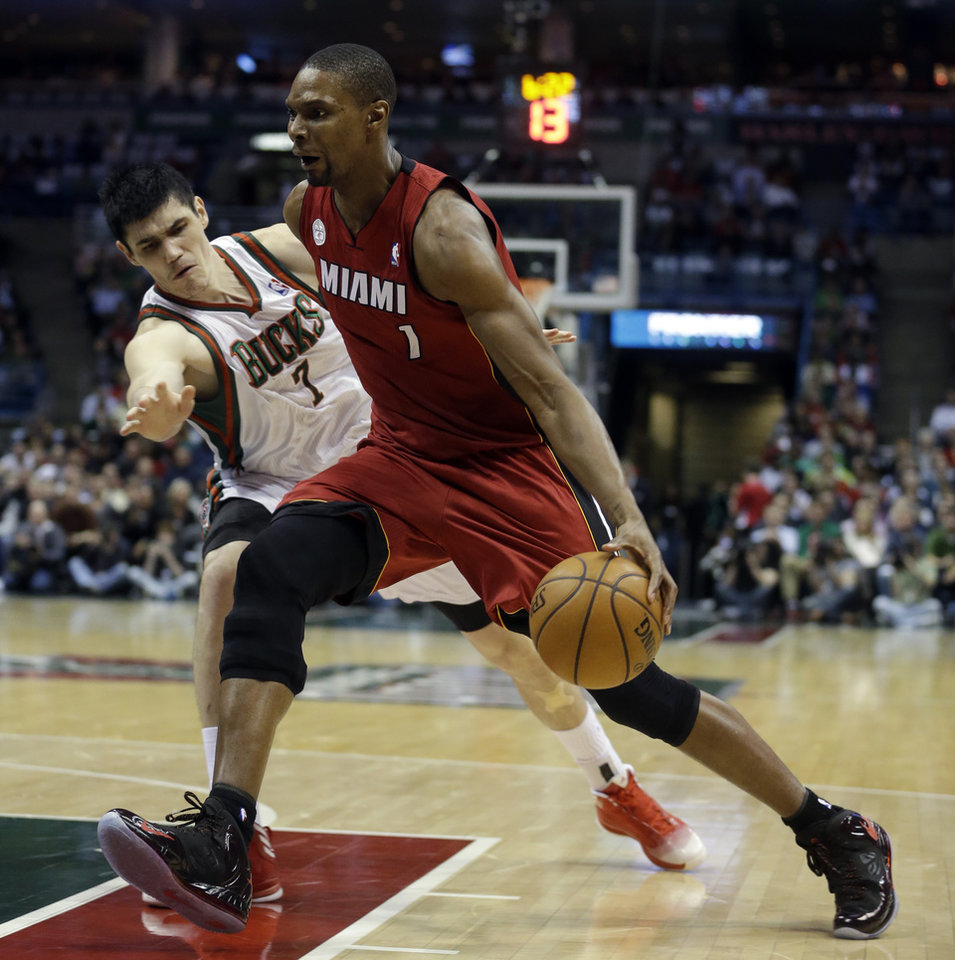 Photo - Miami Heat's Chris Bosh, right, drives past Milwaukee Bucks' Ersan Ilyasova during the first half of Game 3 in their first-round NBA basketball playoff series on Thursday, April 25, 2013, in Milwaukee. (AP Photo/Morry Gash)