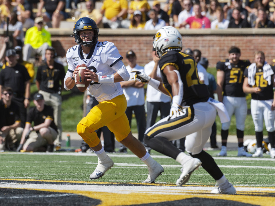 Photo - West Virginia quarterback Austin Kendall, left, looks for an open receiver as he runs from Missouri's Khalil Oliver, right, during the first half of an NCAA college football game Saturday, Sept. 7, 2019, in Columbia, Mo. (AP Photo/L.G. Patterson)