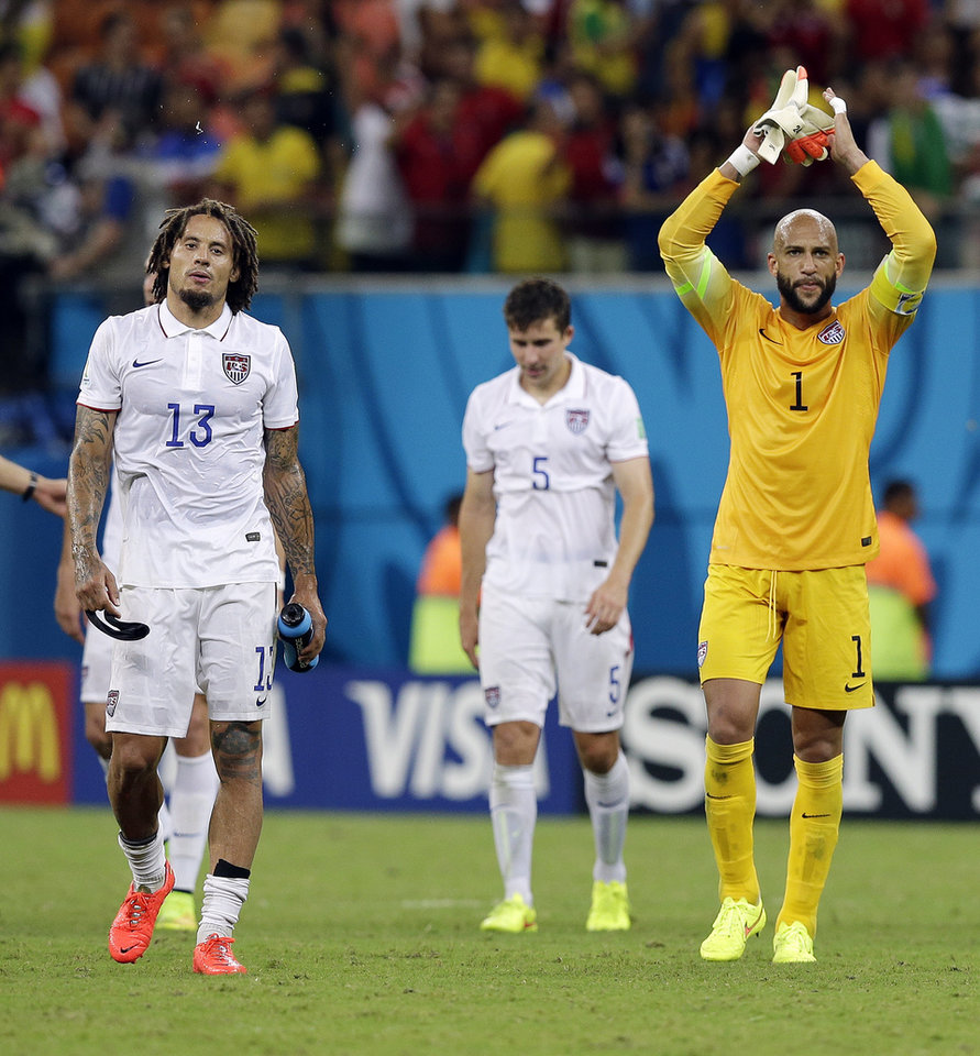 Photo - United States' goalkeeper Tim Howard and United States' Jermaine Jones walk off the pitch following their 2-2 draw with Portugal during the group G World Cup soccer match between the USA and Portugal at the Arena da Amazonia in Manaus, Brazil, Sunday, June 22, 2014. (AP Photo/Martin Mejia)