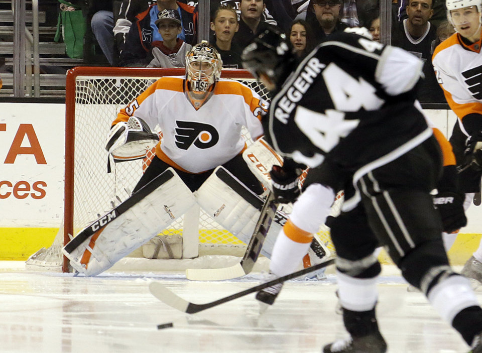 Photo - Philadelphia Flyers goalie Steve Mason (35) waits as Los Angeles KIngs defenseman Robyn Regehr (44) shoots in the first period of an NHL hockey game in Los Angeles Saturday, Feb. 1, 2014.  (AP Photo/Reed Saxon)