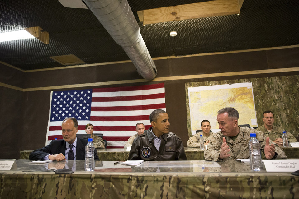 Photo - President Barack Obama, center, is briefed by Marine General Joseph Dunford, commander of the US-led International Security Assistance Force (ISAF), right, and US Ambassador to Afghanistan James Cunningham after arriving at Bagram Air Field for an unannounced visit, on Sunday, May 25, 2014, north of Kabul, Afghanistan. (AP Photo/ Evan Vucci)