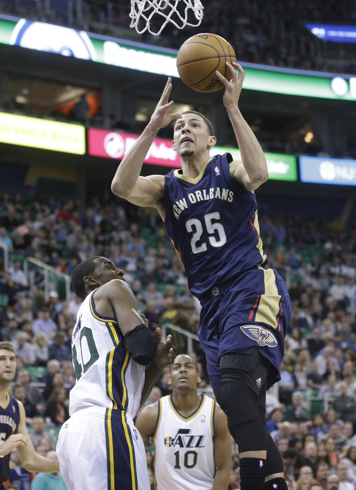 Photo - New Orleans Pelicans' Austin Rivers (25) goes to the basket as Utah Jazz's Jeremy Evans, left, and Alec Burks (10) defend in the second quarter during an NBA basketball game on Friday, April 4, 2014, in Salt Lake City. (AP Photo/Rick Bowmer)