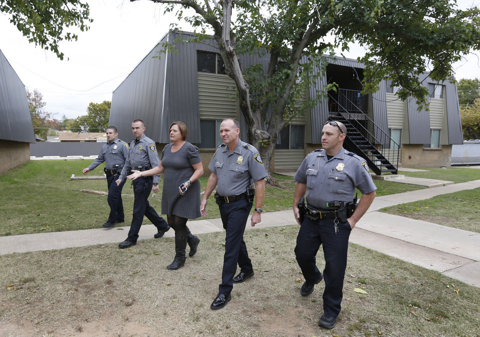 Kay Bale, center, manager of the Mulberry Park apartments on NW 10th street takes a walking tour of her complex with Oklahoma City Police officers, left, Sergeant  Scott Poole, officer Mike Callaway, Master Sergeant Bob Skalla and Sergeant Felix Valadez in Oklahoma City, Monday November 4, 2013. Photo By Steve Gooch, The Oklahoman