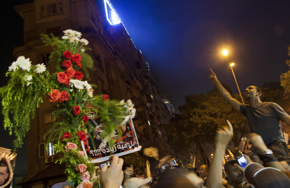 Photo -   An Egyptian man chants anti-Muslim Brotherhood slogans next to a cross made of flowers during a march marking the first anniversary of the victims who were killed during clashes with the military police in front of the National State T.V. building, known as Maspero, in Cairo, Egypt, Tuesday, Oct. 9, 2012. Muslim clerics, Christian priests, activists and former liberal lawmakers were among those marching to mark the anniversary of the