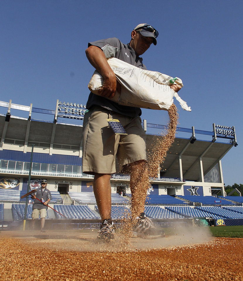 Photo - In this May 22, 2014 photo, Nick McKenna, from Texas A&M, pours calcined clay onto the field at the Southeastern Conference NCAA college baseball tournament in Hoover, Ala. The players and coaches weren't the only ones putting their work on display at the Southeastern Conference baseball tournament. A 40-man grounds crew was laboring to keep the field in good shape. (AP Photo/Butch Dill)