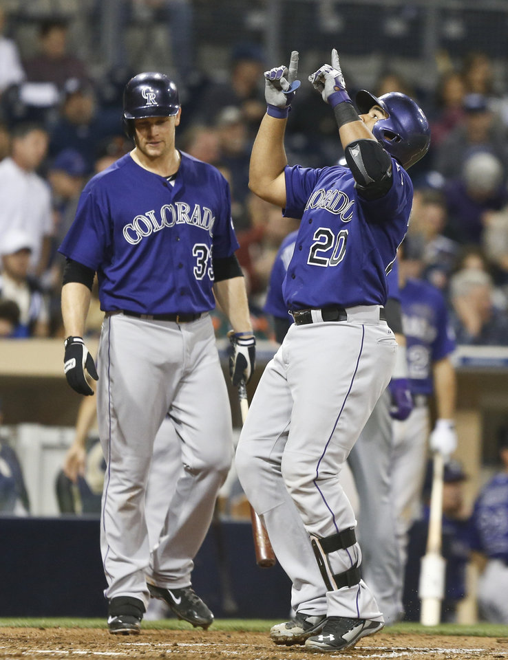 Photo - Colorado Rockies' Wilin Rosario points to heavens as he crosses home plate with a two-run homer against the San Diego Padres in the fifth inning of a baseball game Monday, April 14, 2014, in San Diego. (AP Photo/Lenny Ignelzi)