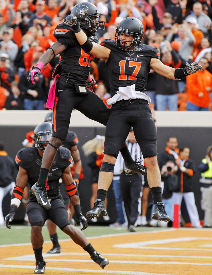 Photo - Oklahoma State's Charlie Moore (17) and Isaiah Anderson (82) celebrate a touchdown catch by Moore in the third quarter during a college football game between Oklahoma State University (OSU) and Texas Christian University (TCU) at Boone Pickens Stadium in Stillwater, Okla., Saturday, Oct. 27, 2012. OSU won, 36-14. Photo by Nate Billings, The Oklahoman