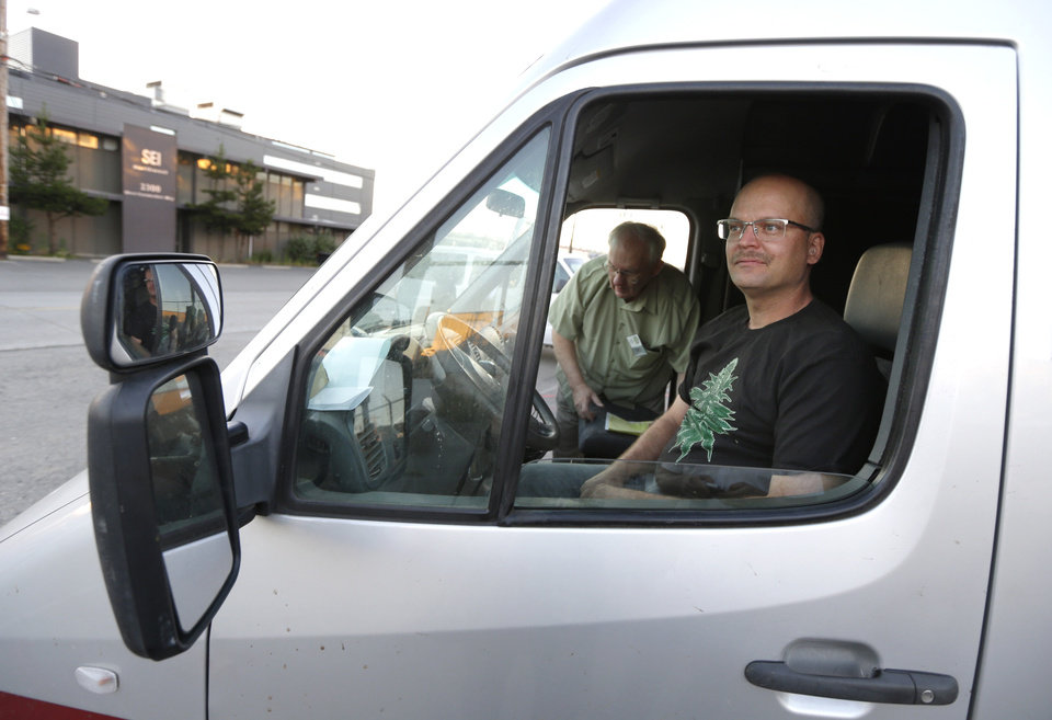Photo - In this July 8, 2014, photo, Phil Tobias, right, director of Sea of Green Farms, prepares to drive a delivery van in Seattle with farm owner Bob Leeds, left, as they set out on their first delivery of recreational marijuana to a store in Bellingham, Wash. It was the first delivery for the company since retail licenses were issued by the state on Monday, July 7. (AP Photo/Ted S. Warren)