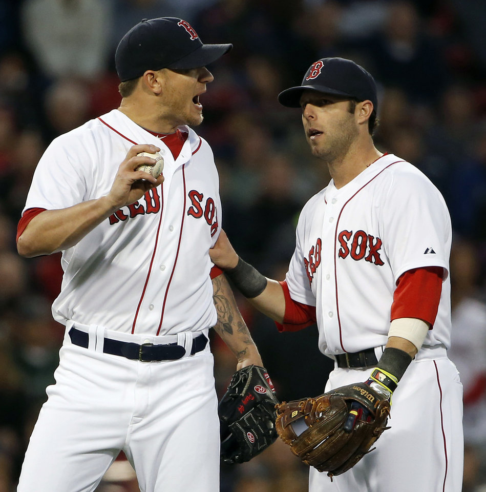 Photo - Boston Red Sox starting pitcher Jake Peavy, left, is restrained by second baseman Dustin Pedroia after Peavy was called for a balk during the fourth inning of a baseball game against the Atlanta Braves at Fenway Park, Thursday, May 29, 2014, in Boston. (AP Photo/Winslow Townson)