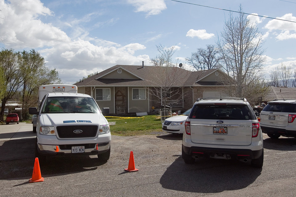 Photo - Authorities investigate a crime scene at a house in Pleasant Grove Utah,  Sunday, April 13, 2014. According to the Pleasant Grove Police Department, seven dead infants were found in the former home of Megan Huntsman, 39. Huntsman was booked into jail on six counts of murder. (AP Photo/Daily Herald, Mark Johnston)