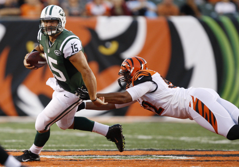 Photo -   New York Jets quarterback Tim Tebow (15) avoids a tackle by Cincinnati Bengals defensive end Jamaal Anderson during the first half of an NFL preseason football game, Friday, Aug. 10, 2012, in Cincinnati. (AP Photo/David Kohl)