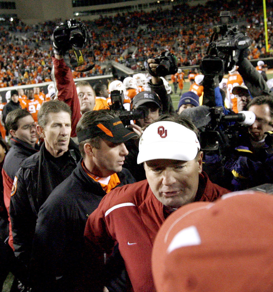 OU coach Bob Stoops and OSU coach Mike Gundy walk away after talking following the college football game between the University of Oklahoma Sooners (OU) and Oklahoma State University Cowboys (OSU) at Boone Pickens Stadium on Saturday, Nov. 29, 2008, in Stillwater, Okla. STAFF PHOTO BY BRYAN TERRY