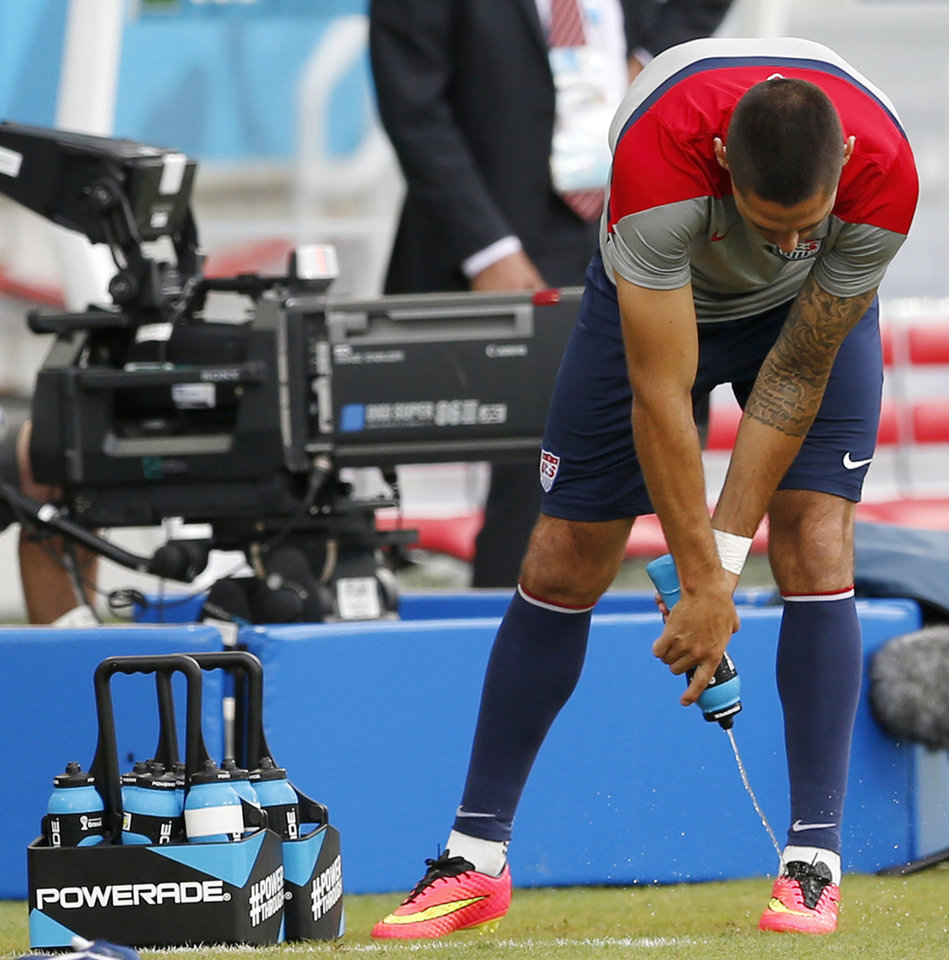 Photo - United States' Clint Dempsey uses a Powerade bottle to spray liquid on his soccer boots during an official training session the day before the group G World Cup soccer match between Ghana and the United States at the Arena das Dunas in Natal, Brazil, Sunday, June 15, 2014.  (AP Photo/Julio Cortez)