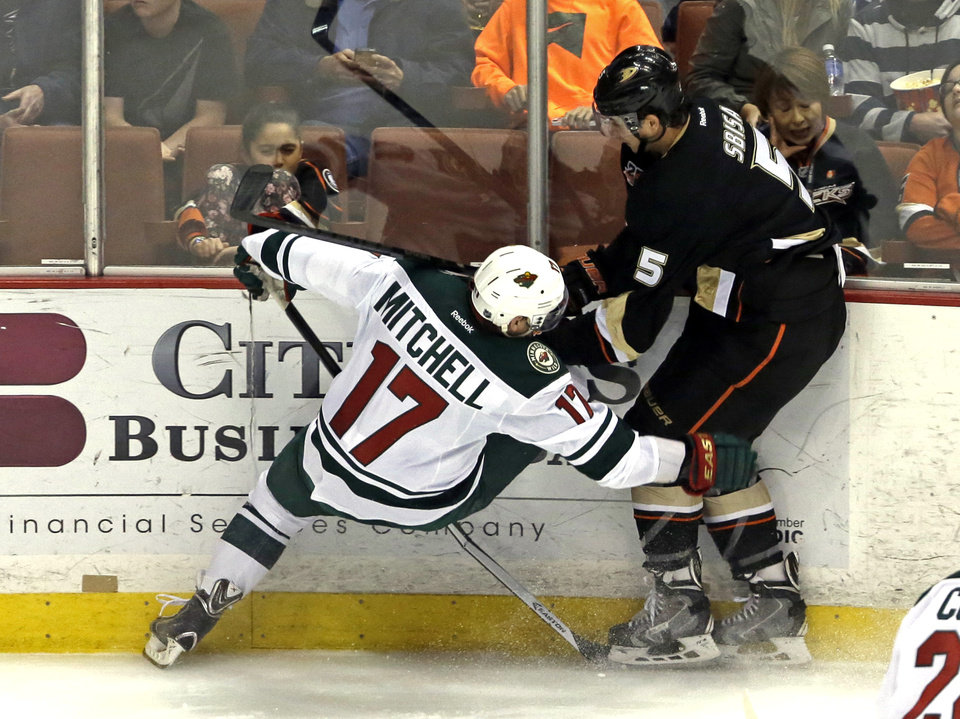 Photo - Anaheim Ducks defenseman Luca Sbisa (5), of Italy, and Minnesota Wild center Torrey Mitchell (17) tangle in the first period of an NHL hockey game in Anaheim, Calif., Tuesday, Jan. 28, 2014. (AP Photo/Reed Saxon)