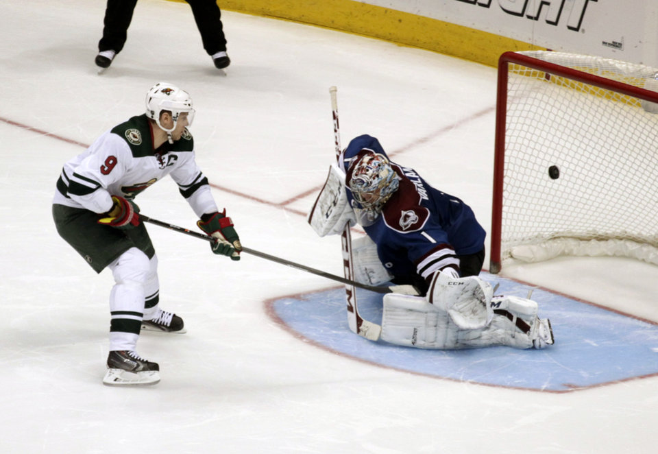 Minnesota Wild center Mikko Koivu (9) scores the game-winning shootout goal against Colorado Avalanche goalie Semyon Varlamov (1) in an NHL hockey game in Denver on Saturday, Dec. 14, 2013. Minnesota won in the shootout after a 1-1 tie in regulation. (AP Photo/Joe Mahoney)