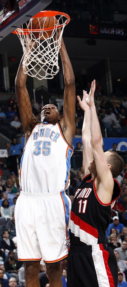 Photo - Oklahoma City's Kevin Durant (35) dunks the ball over Sergio Rodriguez (11) of the Blazers during the NBA basketball game between the Oklahoma City Thunder and the Portland Trail Blazers at the Ford Center in Oklahoma City, Friday, February 6, 2009. BY NATE BILLINGS, THE OKLAHOMAN