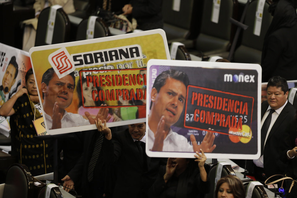 Photo - Opposition lawmakers hold up banners showing photos of Mexico's president-elect Enrique Pena Nieto, saying