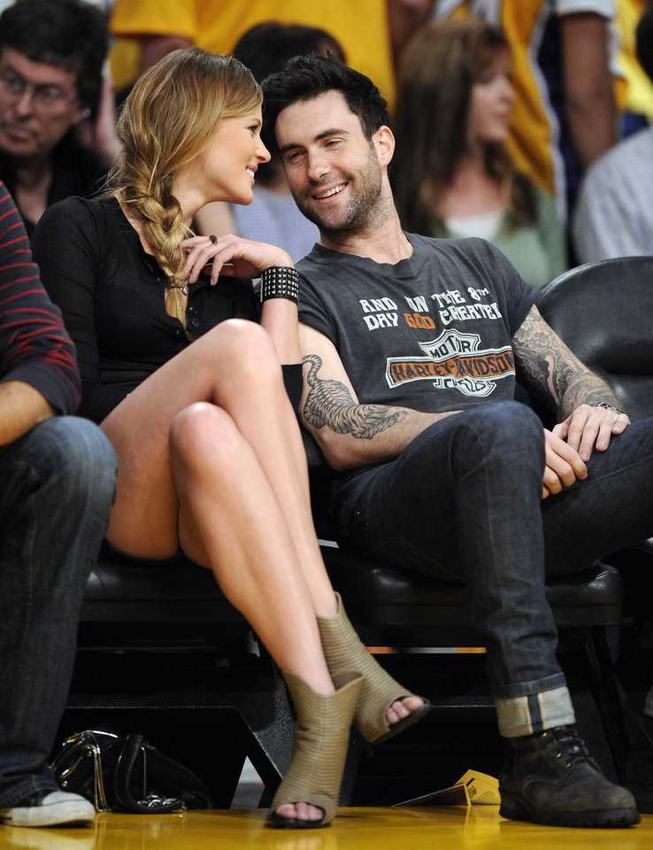 Photo -  Maroon 5 lead singer Adam Levine, right, sits with a friend as they watch the Los Angeles Lakers play the Oklahoma City Thunder in the NBA basketball playoffs Sunday, April 18, 2010, in Los Angeles. (AP Photo/Mark J. Terrill) ORG XMIT: LAS112