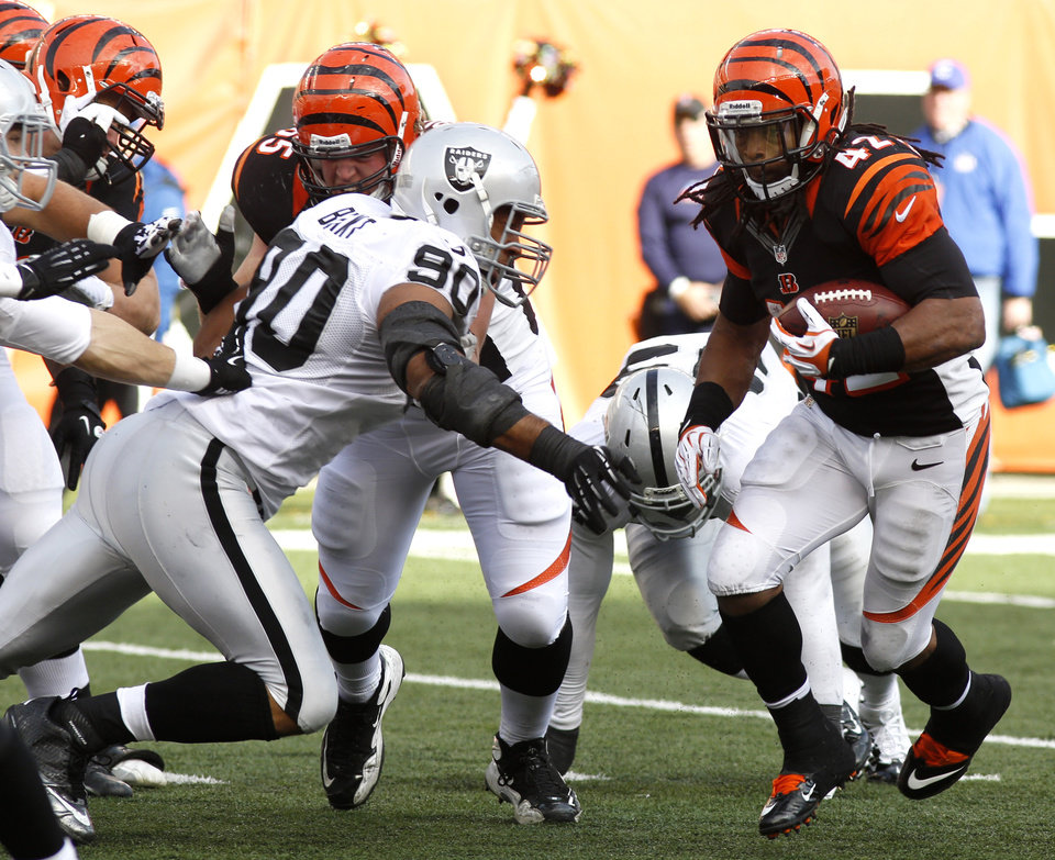 Cincinnati Bengals running back BenJarvus Green-Ellis (42) runs against Oakland Raiders defensive tackle Desmond Bryant (90) in the first half of an NFL football game, Sunday, Nov. 25, 2012, in Cincinnati. (AP Photo/David Kohl)