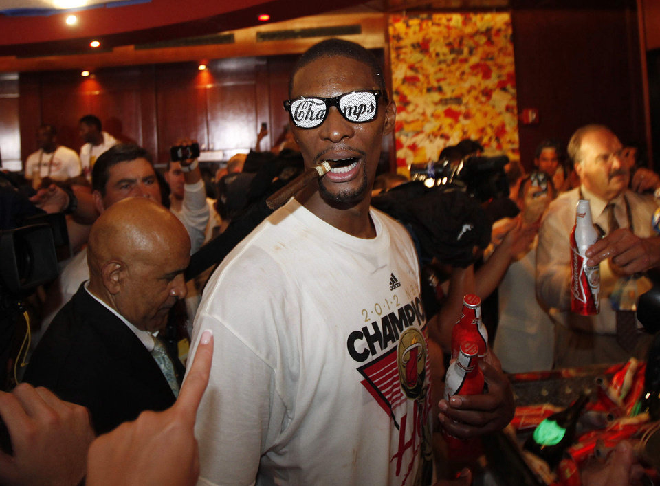 Photo -   The Miami Heat's Chris Bosh celebrates in the locker room after Game 5 of the NBA finals basketball series against the Oklahoma City Thunder, Friday, June 22, 2012, in Miami. The Heat won 121-106 to become the 2012 NBA Champions.(AP Photo/Wilfredo Lee)