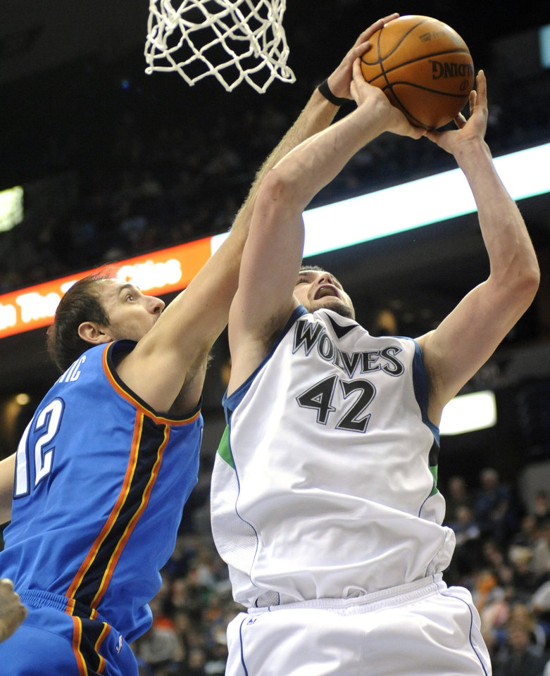 Photo - Oklahoma City Thunder's Nenad Krstic (12) fouls Minnesota Timberwolves' Kevin Love (42) during the second quarter of an NBA basketball game in Minneapolis on Sunday, Feb. 21, 2010. The Thunder won 109-107. (AP Photo/Hannah Foslien) ORG XMIT: MNHF104