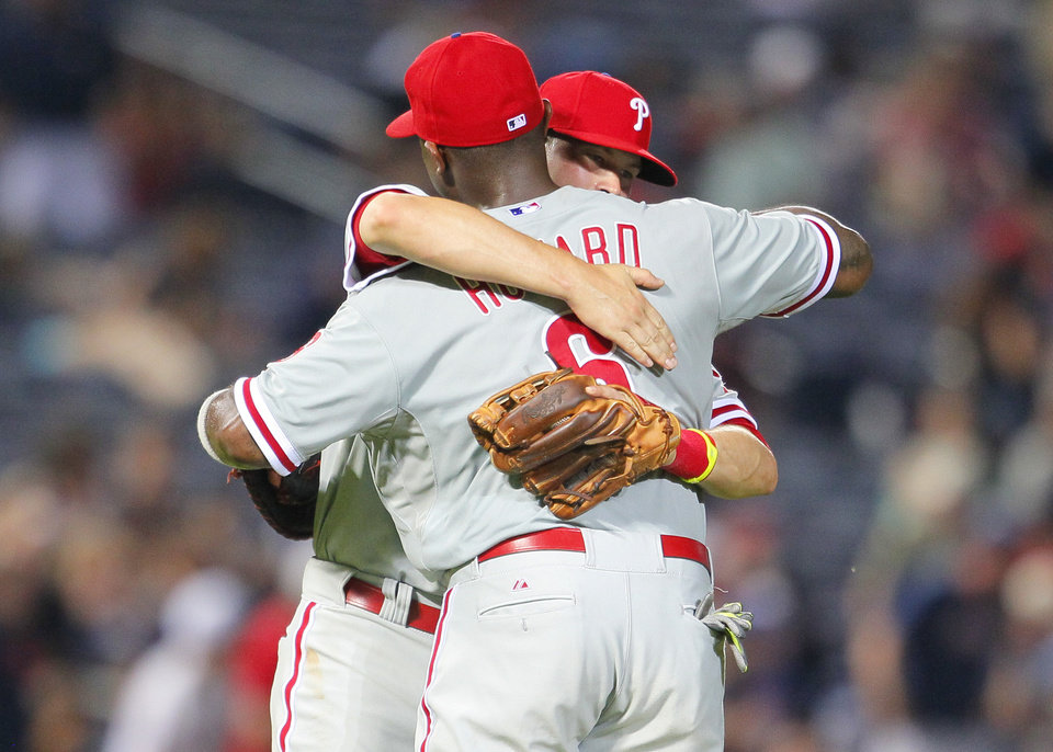 Photo - Philadelphia Phillies first baseman Ryan Howard (6) celebrates with third baseman Reid Brignac (17) after the win in a baseball game against the Atlanta Braves Tuesday, June 17, 2014, in Atlanta. (AP Photo/Todd Kirkland)