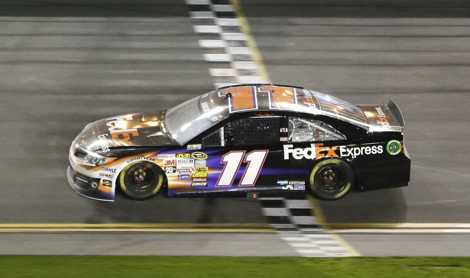 Photo - Denny Hamlin crosses the finish line to win the NASCAR Sprint Unlimited auto race at Daytona International Speedway in Daytona Beach, Fla., Saturday, Feb. 15, 2014. (AP Photo/John Raoux)