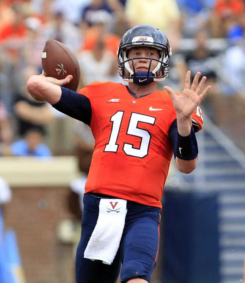Photo - Virginia quarterback Matt Johns (15) throws a pass during the second half of an NCAA college football game against UCLA at Scott Stadium, Saturday, Aug. 30, 2014, in Charlottesville, Va. UCLA won 28-20. (AP Photo/Andrew Shurtleff)