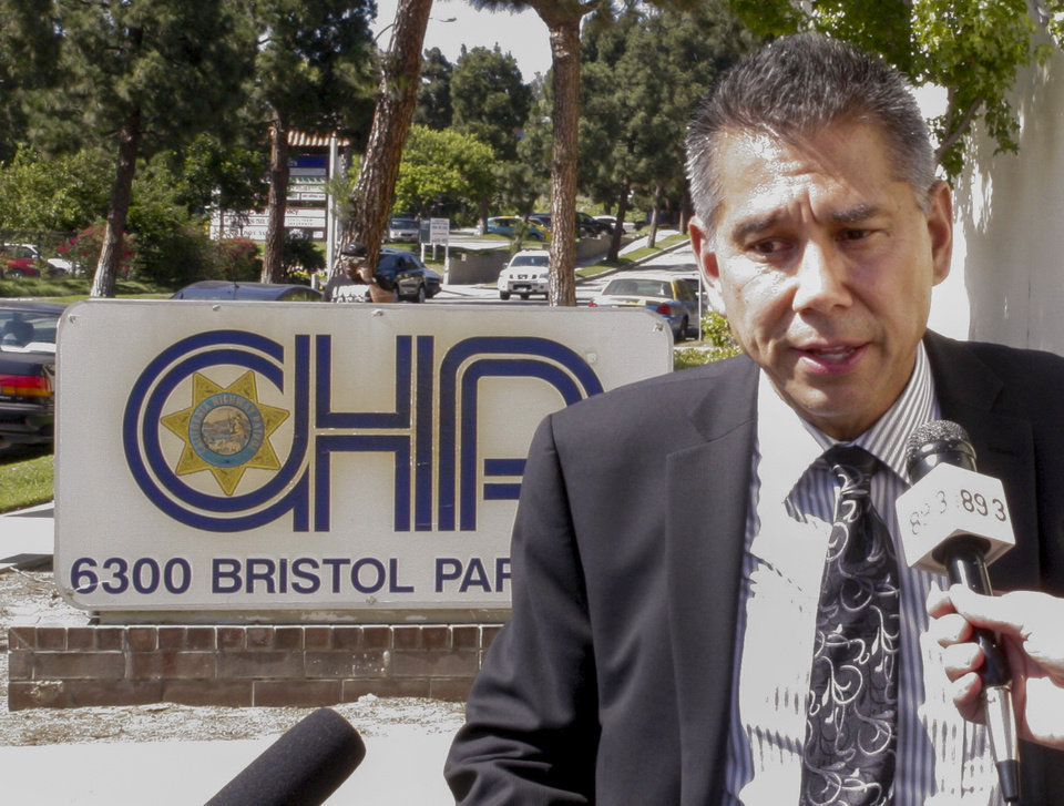 Photo - California Highway Patrol Commissioner Joe Farrow takes question from the media outside the CHP offices after a meeting with a group of community activists demanding action in response to a cellphone video showing an officer repeatedly punching a woman, in Culver City, Calif., Tuesday, July 8, 2014. (AP Photo/Tami Abdollah)