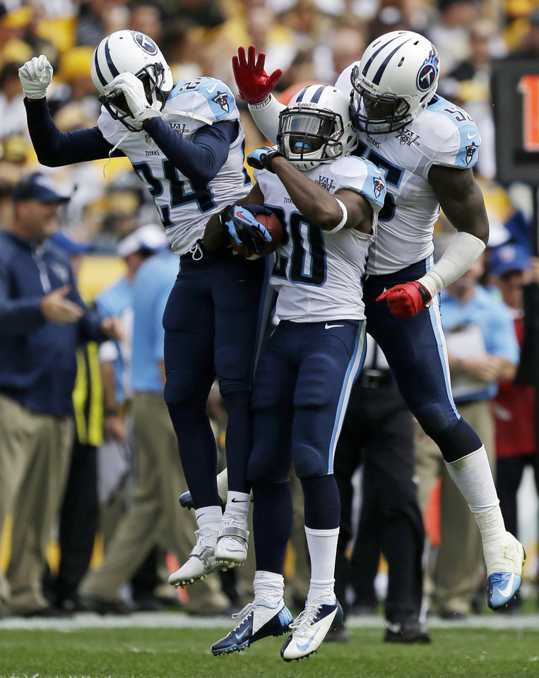 Photo - Tennessee Titans cornerback Alterraun Verner (20) celebrates with teammates Coty Sensabaugh (24) and Zach Brown (55) after intercepting a pass by Pittsburgh Steelers quarterback Ben Roethlisberger (7) during the second quarter of an NFL football game in Pittsburgh, Sunday, Sept. 8, 2013. The Titans won 16-9. (AP Photo/Gene J. Puskar)