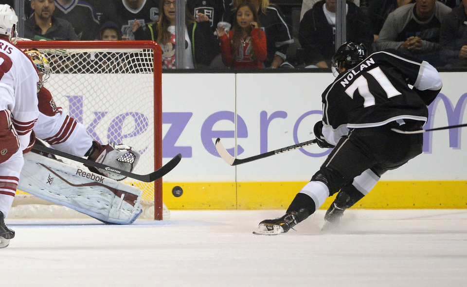 Photo - Los Angeles Kings center Jordan Nolan, right, scores against Phoenix Coyotes goalie Mike Smith during the first period of their NHL hockey game on Thursday, Oct. 24, 2013, in Los Angeles. (AP Photo/Mark J. Terrill)