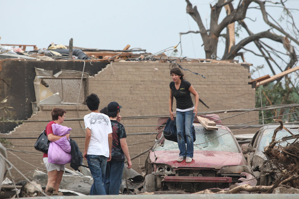 Photo - Residents attempt to retrieve their belongings after a tornado destroyed their apartments Wednesday, April 27, 2011 Tuscaloosa, Ala. A wave of severe storms laced with tornadoes strafed the South on Wednesday, killing at least 16 people around the region and splintering buildings across swaths of an Alabama university town. (AP Photo/Caroline Summers)