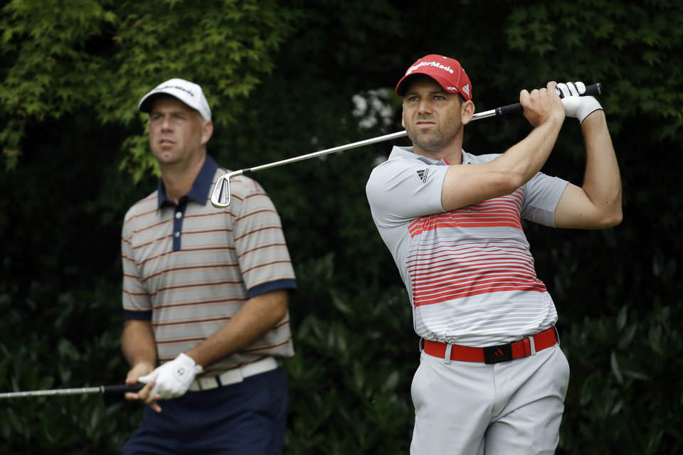 Photo - Sergio Garcia, right, of Spain, and Stewart Cink watch Garcia's tee shot on the 11th hole during the first round of the U.S. Open golf tournament at Merion Golf Club, Thursday, June 13, 2013, in Ardmore, Pa. (AP Photo/Morry Gash)