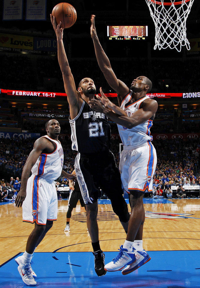 San Antonio\'s Tim Duncan (21) shoots against Oklahoma City\'s Serge Ibaka (9) as Kendrick Perkins (5) looks on during an NBA basketball game between the Oklahoma City Thunder and the San Antonio Spurs in Oklahoma City Monday, Dec. 17, 2012. Oklahoma City won, 107-93. Photo by Nate Billings, The Oklahoman