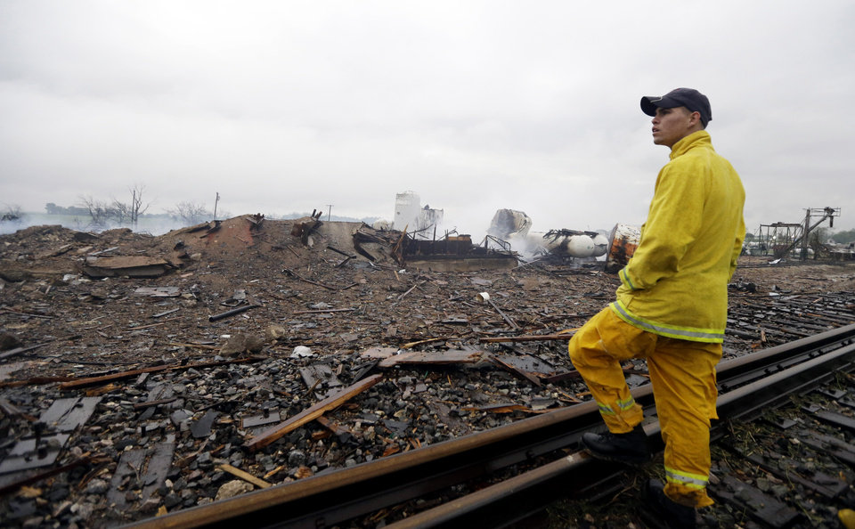 Photo - A firefighter stands on a rail line and surveys the remains of a fertilizer plant destroyed by an explosion in West, Texas, Thursday, April 18, 2013.  A massive explosion at the West Fertilizer Co. killed as many as 15 people and injured more than 160, officials said overnight.  (AP Photo/LM Otero)