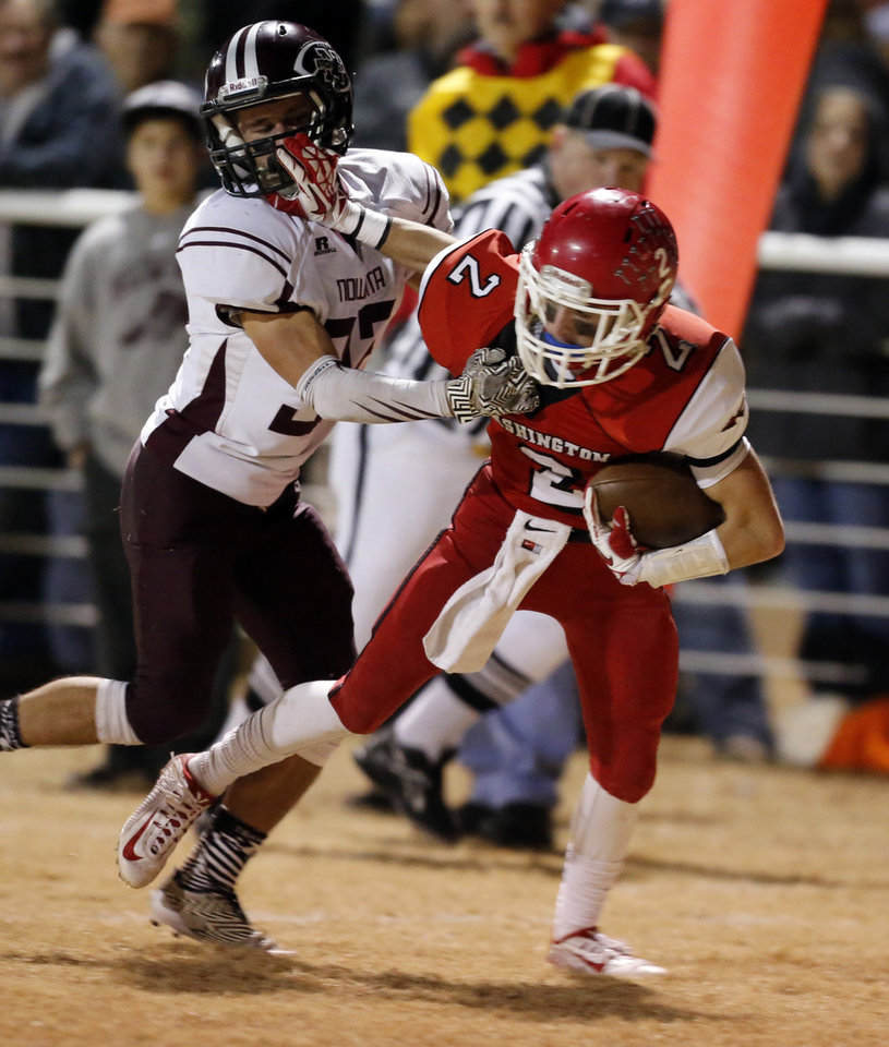 Photo - Washington's Brady Kulbeth runs trying to avoid Wyatt Sanders as the Nowata Ironmen play the Washington Warriors in high school football on Friday, Nov. 28, 2014 in Washington, Okla. Photo by Steve Sisney, The Oklahoman