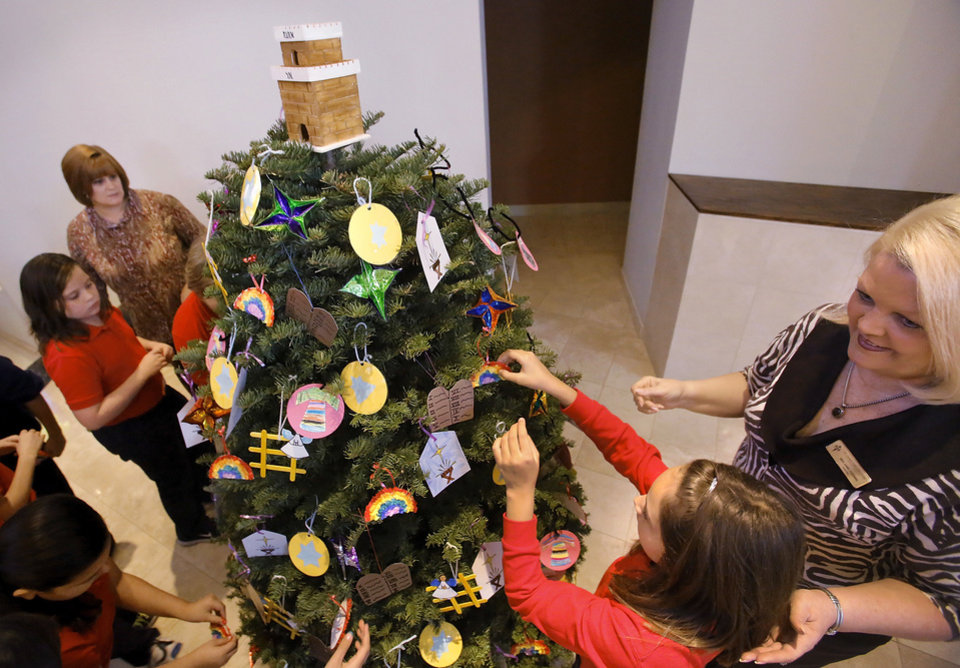 Fourth grade students from St. James Catholic School hang their ornaments on the Jesse tree with help from the school's principal Anne Codding. Photo By Jim Beckel, The Oklahoman  <strong>Jim Beckel - THE OKLAHOMAN</strong>