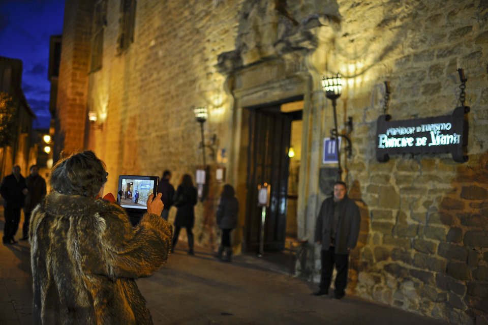 A tourist  takes photos of the entrance at parador hotel of Principe de Viana is seen in Olite, northern  Spain on Friday, Dec. 7, 2012. Employees of Spain's premium hotel chain Parador, a state-run group that uses castles, monasteries and palaces, are holding a two-day strike to protest job cuts and possible closures. The Parador hotels group, which started in 1928, says a drop in demand could leave it with accumulated losses of €107 million ($140 million) by the end of the year. It intends to cut 644 jobs out of a workforce of 4,400. (AP Photo/Alvaro Barrientos)