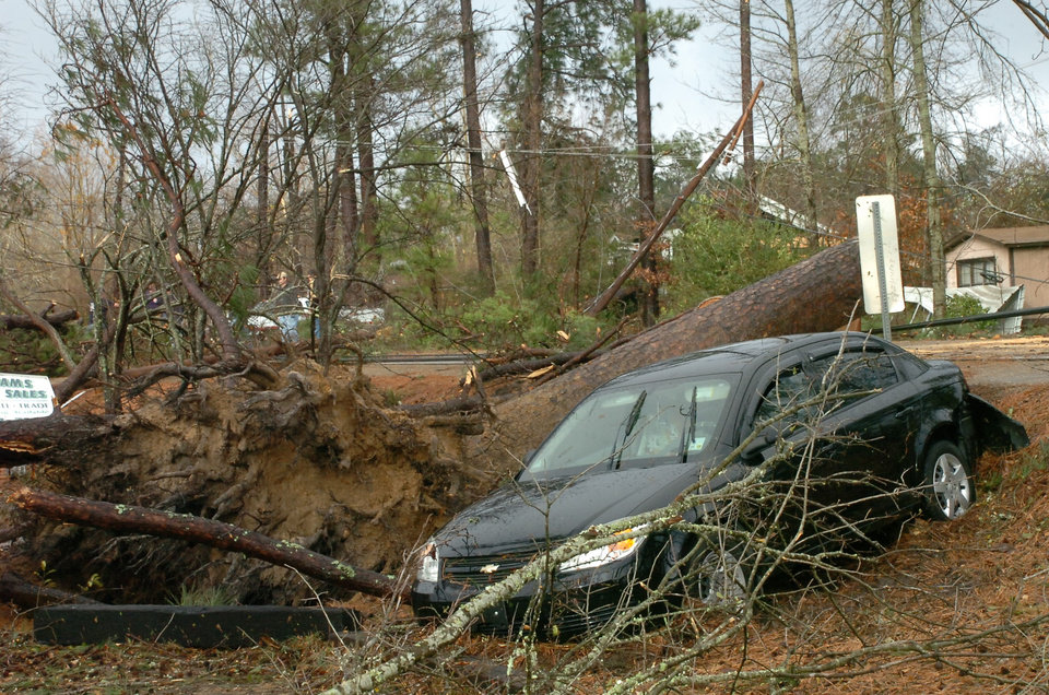 Photo - Geraldine Pedersen and her dog Marlow were in her car traveling down U.S. 71 in the Tioga, Louisiana area when a tree fell down in front of the car and a wind knocked her car into a yard, Tuesday, Dec. 25, 2012. A tornado through the Central Louisiana area. (AP Photo/The Town Talk, Melinda Martinez)