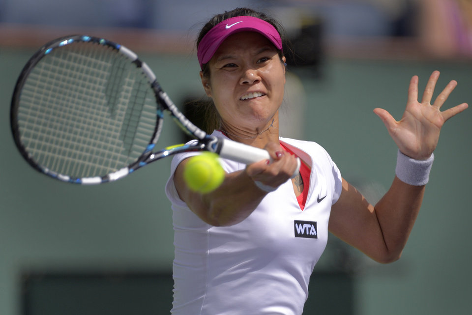 Photo - Li Na, of China, hits a return to Dominika Cibulkova, of Slovakia, during a quarterfinal match at the BNP Paribas Open tennis tournament, Thursday, March 13, 2014 in Indian Wells, Calif. (AP Photo/Mark J. Terrill)