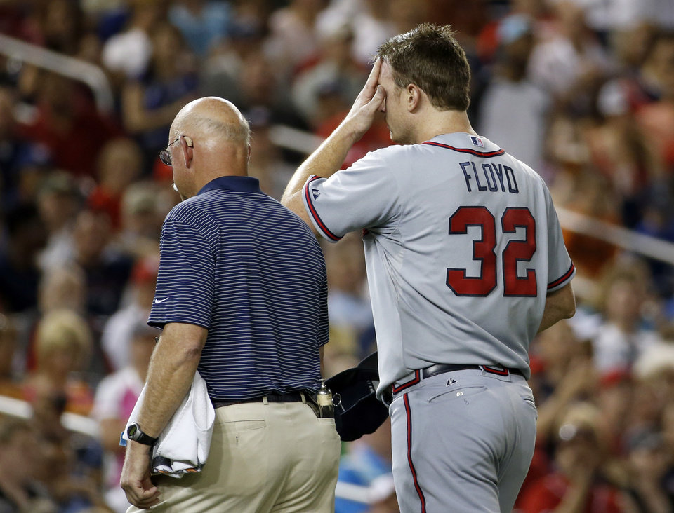 Photo - Atlanta Braves head athletic trainer Jeff Porter escorts Atlanta Braves starting pitcher Gavin Floyd off their field during the seventh inning of a baseball game against the Washington Nationals at Nationals Park Thursday, June 19, 2014, in Washington. The Braves won 3-0. Atlanta Braves right-hander Gavin Floyd left Thursday night's game against the Washington Nationals with an elbow injury in his ninth start since returning from Tommy John surgery. (AP Photo/Alex Brandon)