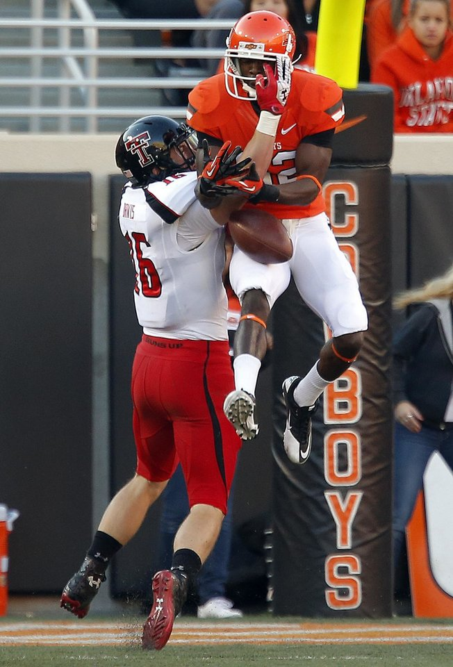 Photo - Oklahoma State's Isaiah Anderson (82) catches a touchdown pass as Texas Tech's Cody Davis (16) defends during a college football game between Oklahoma State University and the Texas Tech University (TTU) at Boone Pickens Stadium in Stillwater, Okla., Saturday, Nov. 17, 2012. Photo by Sarah Phipps, The Oklahoman